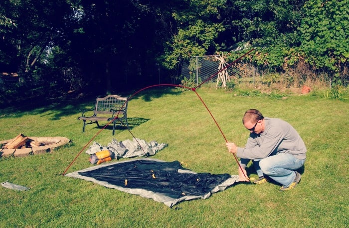 Setting up a camping tent in the backyard.