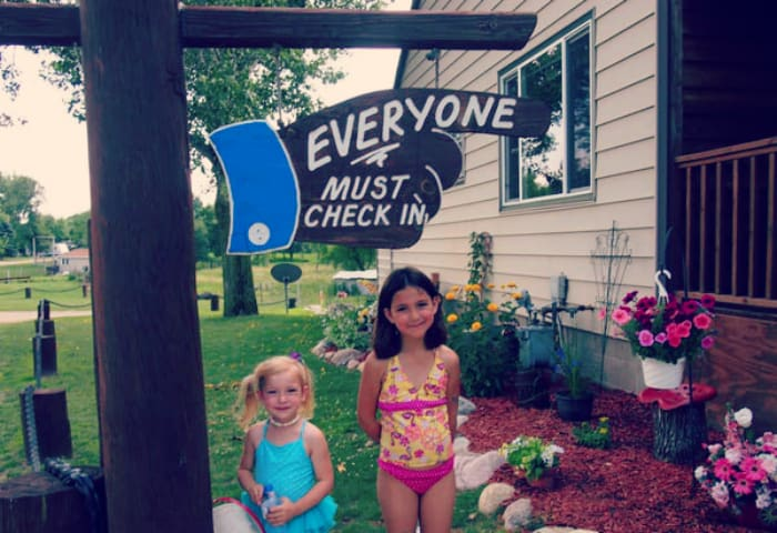 Kids standing in front of check-in sign at campground.