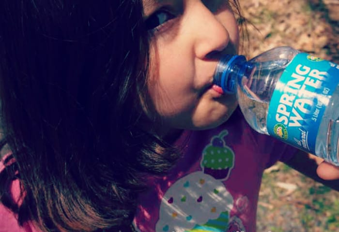 Girl drinking bottled water while camping.