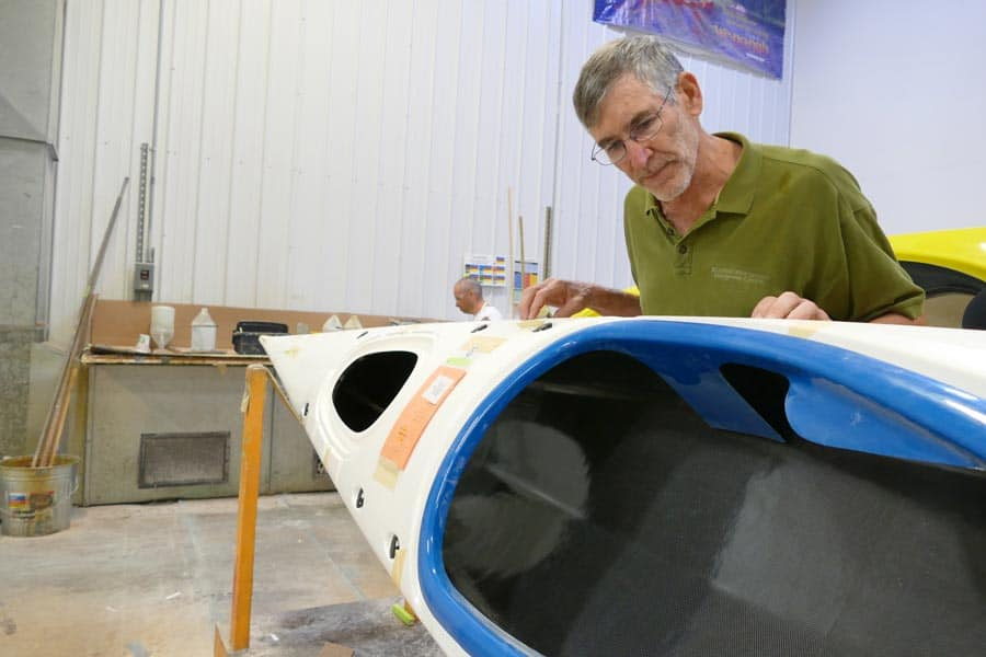 Mike inspecting a Current Designs kayak to see where it is shipping to.