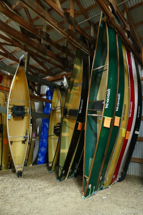 Canoes of different sizes and colors in storage at Wenonah Canoe