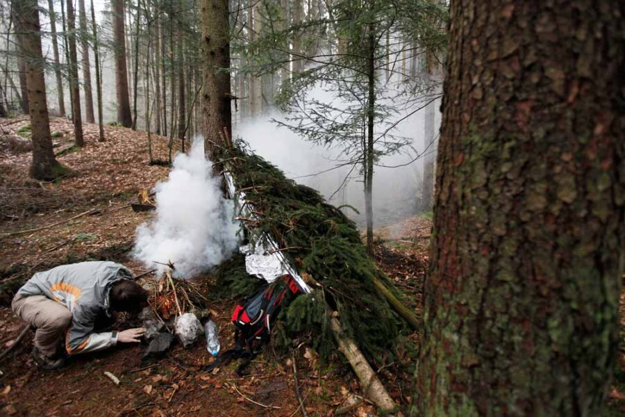 Photo of person starting a campfire and creating a shelter while surviving in the wilderness.