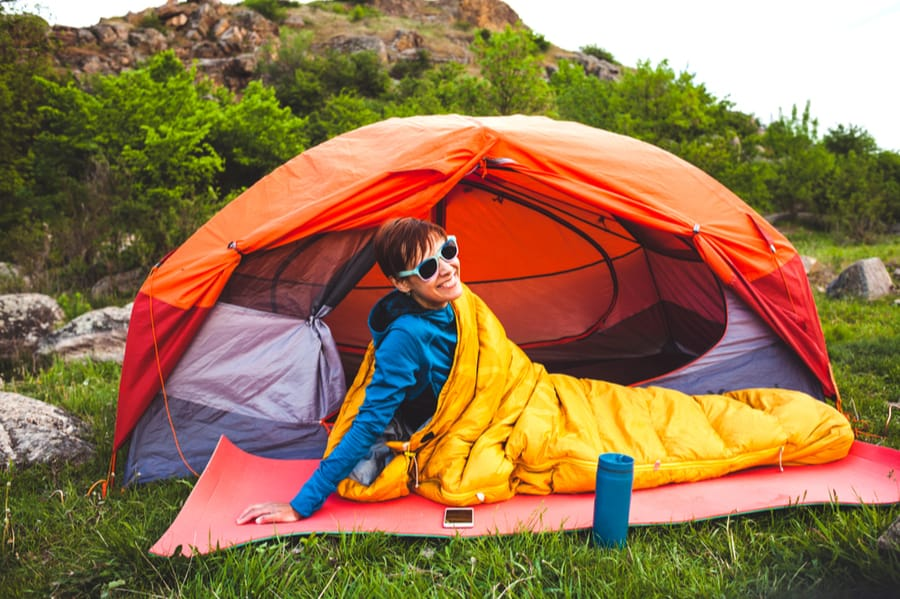 Woman in Sleeping Bag Outside of Tent