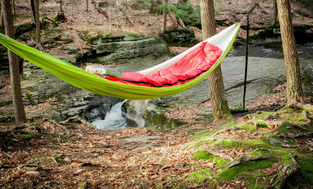 Hammock Camping - Green Hammock with red sleeping bag.
