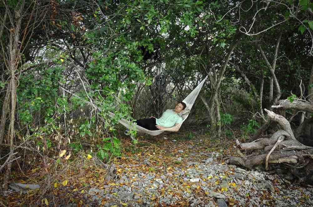 Man sleeps in Mexican hammock under trees in jungle