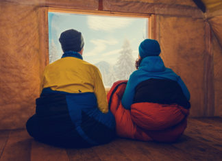 Two Campers Sit in Winter Sleeping Bags