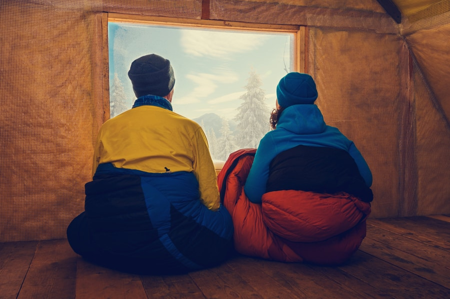 Two Campers Sit in Winter Sleeping Bags