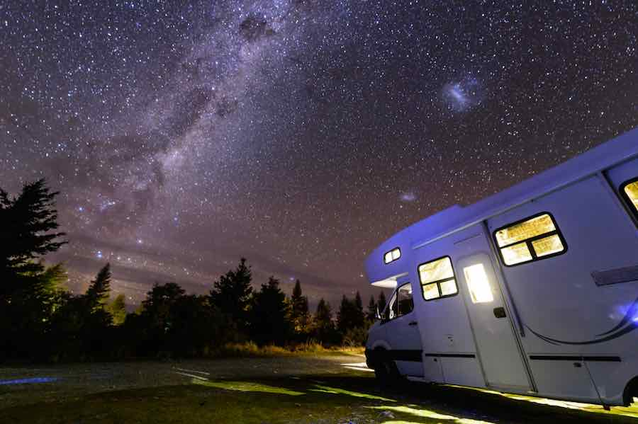 Motorhome parked in the woods on a starry night.