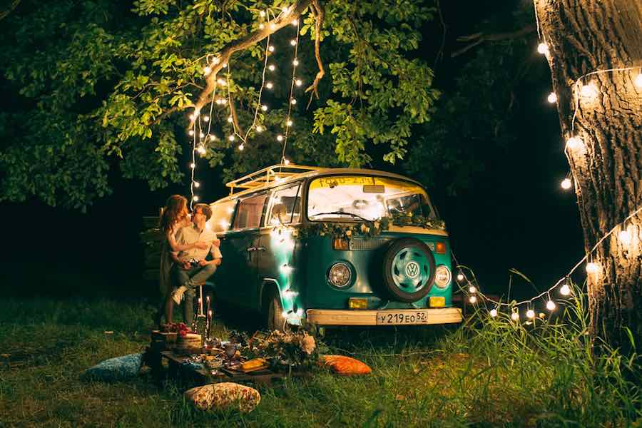 old VW camper van at night with string lights hanging in a tree.