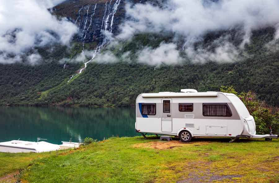 travel trailer camping next to a lake.