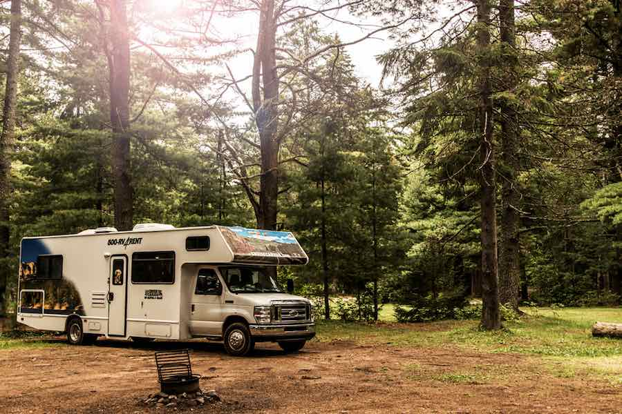 Buying A Class B RV - RV at campsite in the woods.