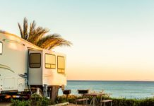 RV Buyers Guide - Travel Trailer on Florida coast with ocean and palm tree