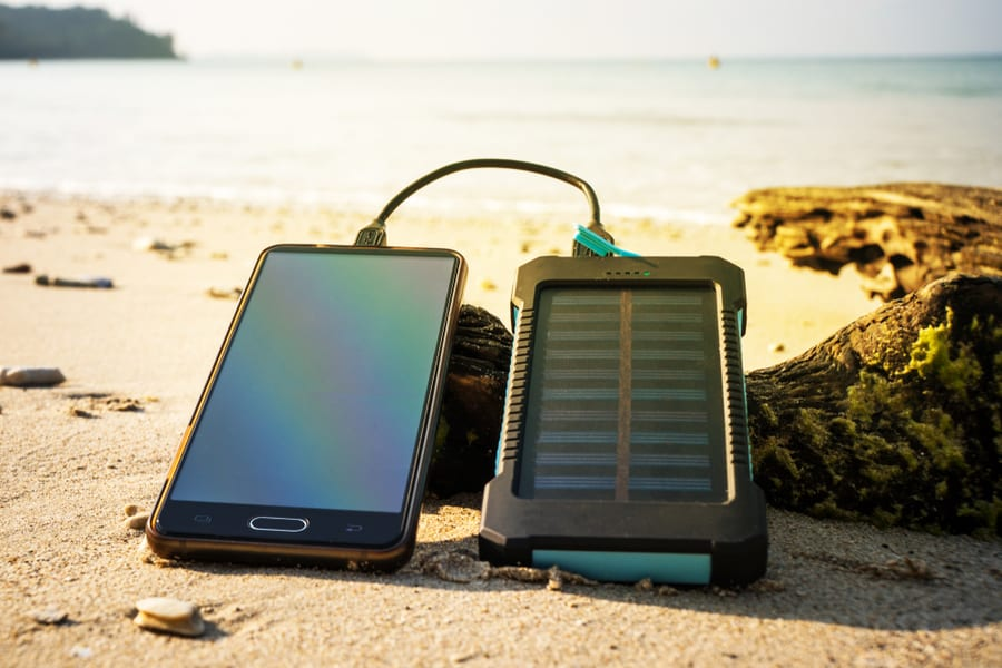 Portable Solar panels for camping set up along the beach charging a phone.