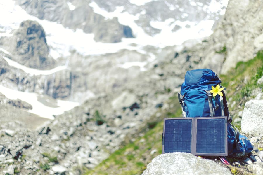 Portable Solar Panel set up next to a backpack on a mountain camping trip.