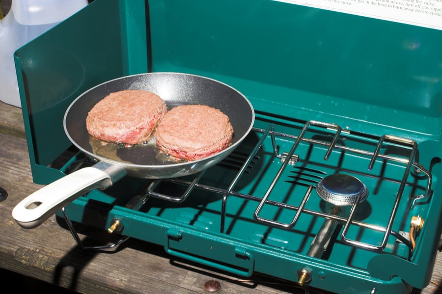 Cooking hambrugers on a camp stove