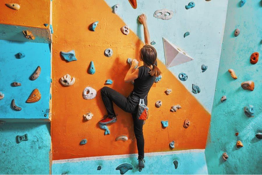 Woman Rock Climbing at an Indoor Climbing Gym