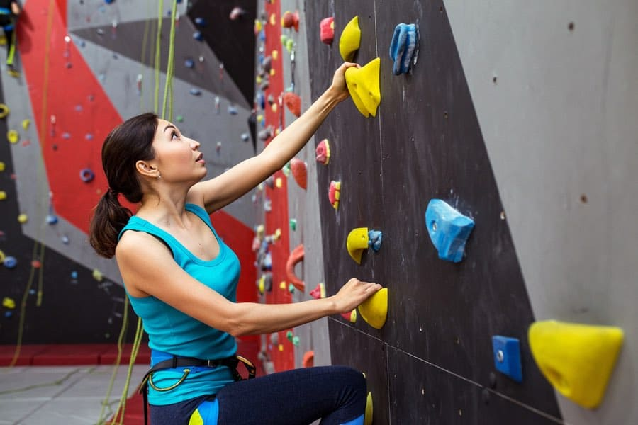 Woman Practicing Rock Climbing on an Indoor Rock Wall