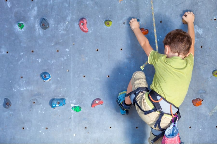 Young Child Rock Climbing on an Indoor Climbing Wall
