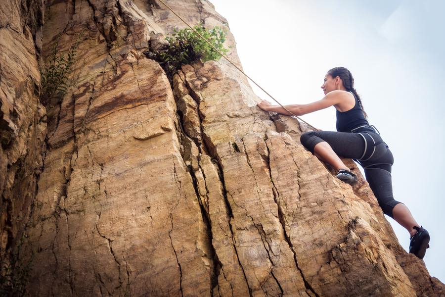 Woman Rock Climbing Outdoors With Rope and Harness