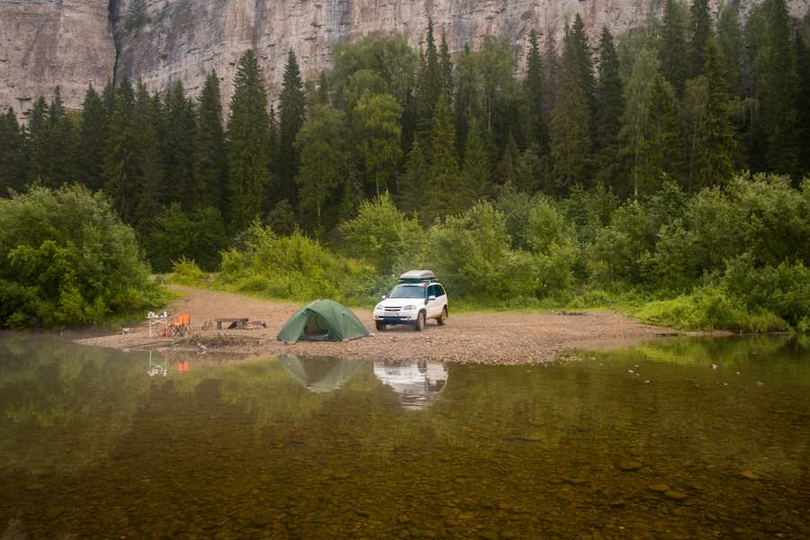 car camping on a beach on the lake with mountains in the background