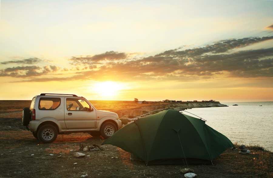 Car camping on a lake at sunset.