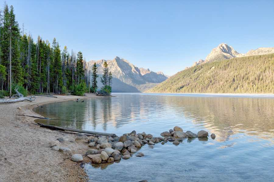 Trees, beach, water, and mountains at Redfish Lake in Idaho