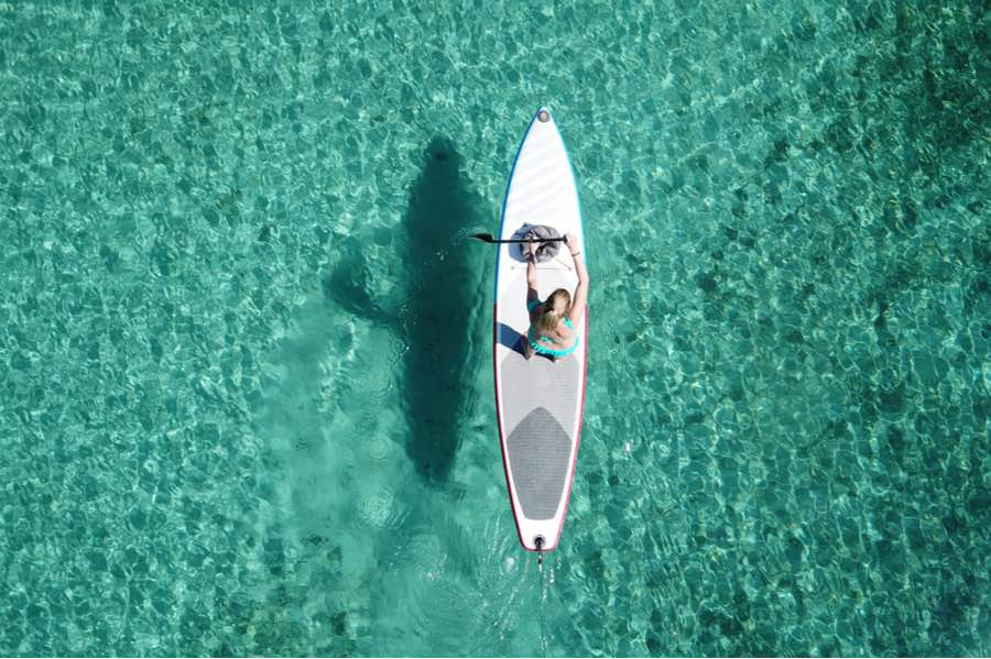 Bird's Eye View of Woman SUPing on Clear Blue Water