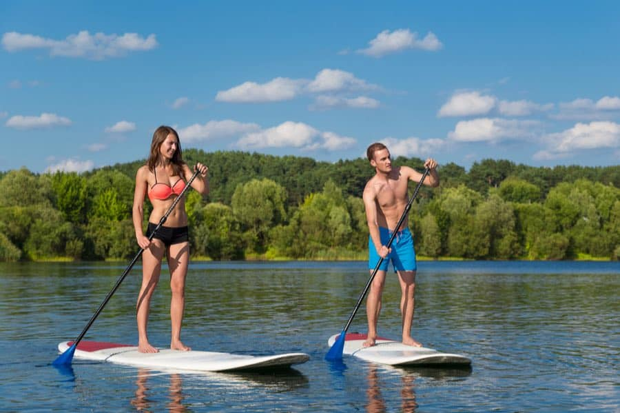 Man and Woman SUPing on River