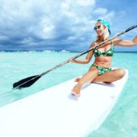 Woman Stand Up Paddleboarding on Blue Water