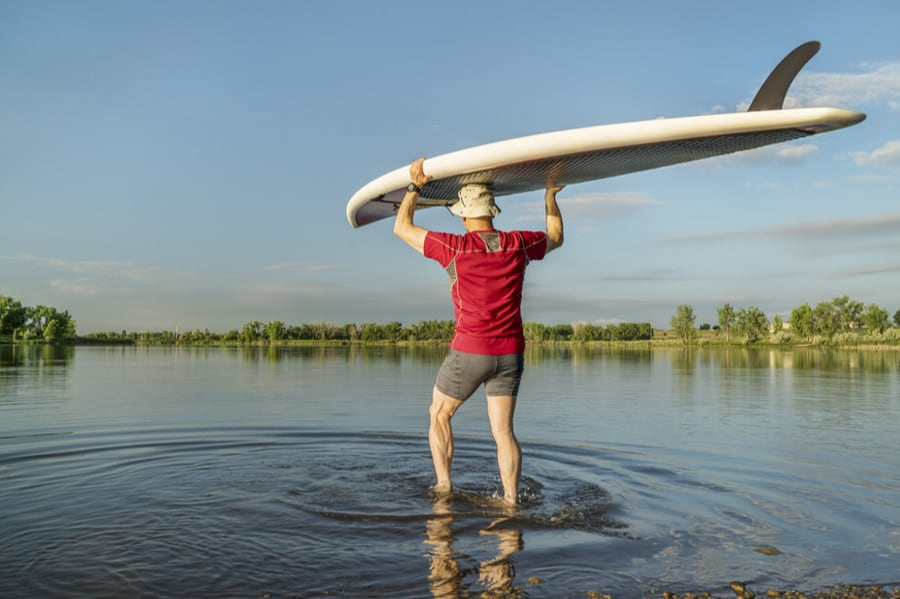 Man Hauling Stand Up Paddleboard Into Water