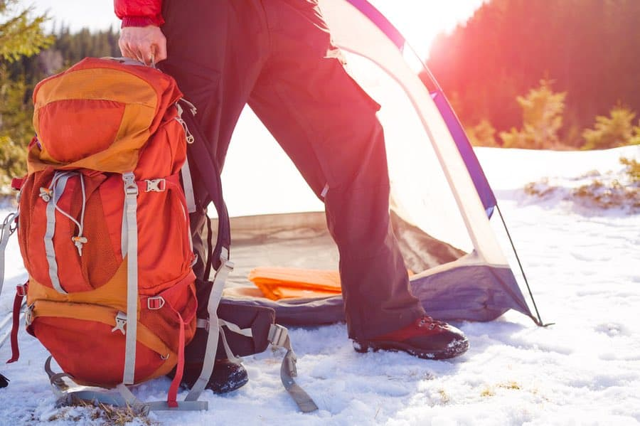 Man Holding Backpack Near Tent in Winter