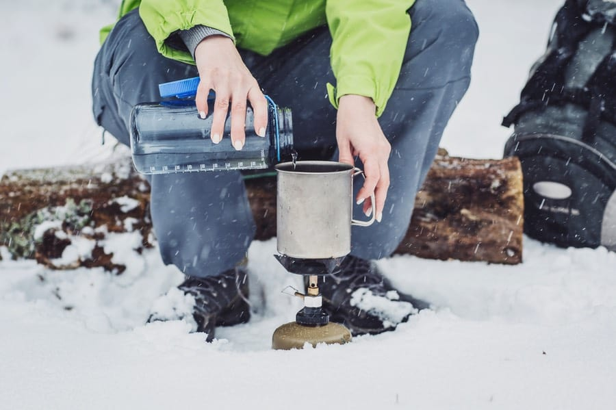 Woman Pouring Water Into Winter Backpacking Stove