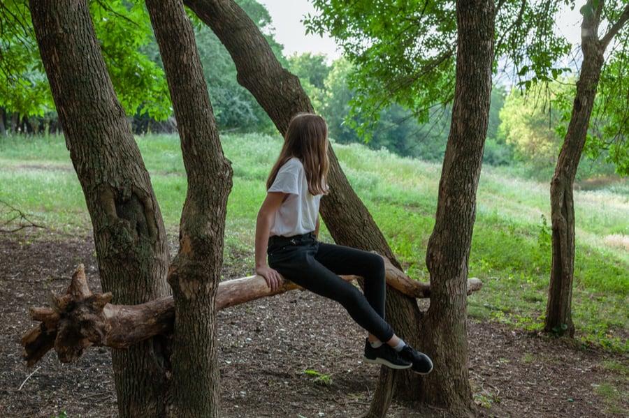 Girl Sitting On Log in Woods