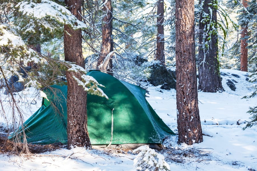 Photo of green camping tent in the winter.