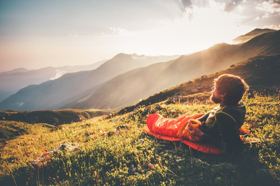 Man Laying in a Backpacking Sleeping Bag Looking Out Over Backcountry