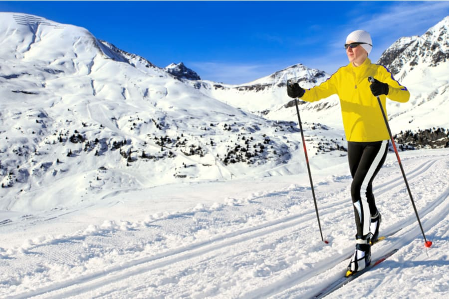 Woman Cross-Country Skiing in Mountains