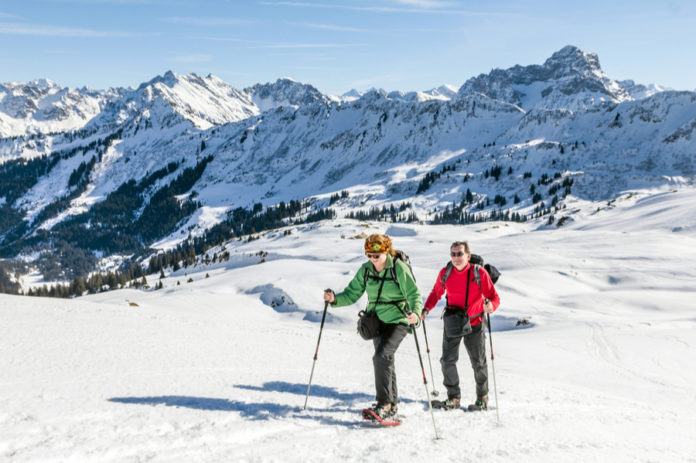 Couple Snowshoeing in Mountains