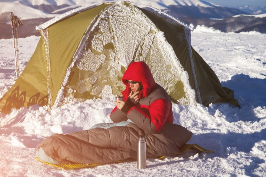 Man in Sleeping Bag Outside in Snow in Front of Tent