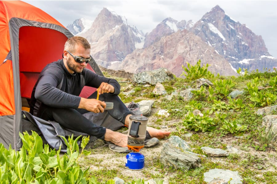 Man Eating a Backpacking Meal on Top of Mountain