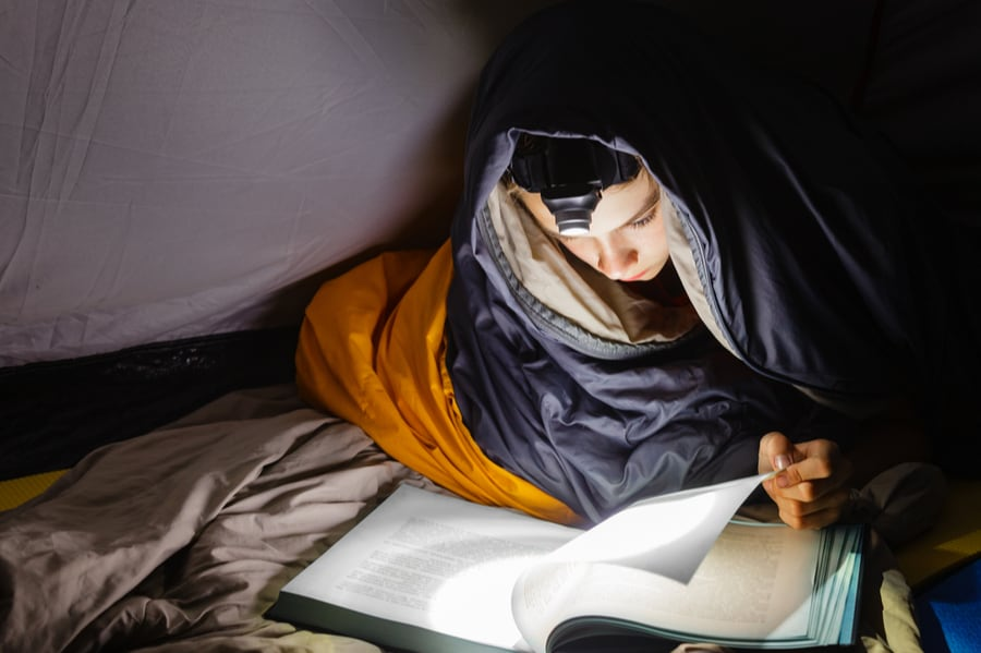 Child reading a book by headlamp in a tent.