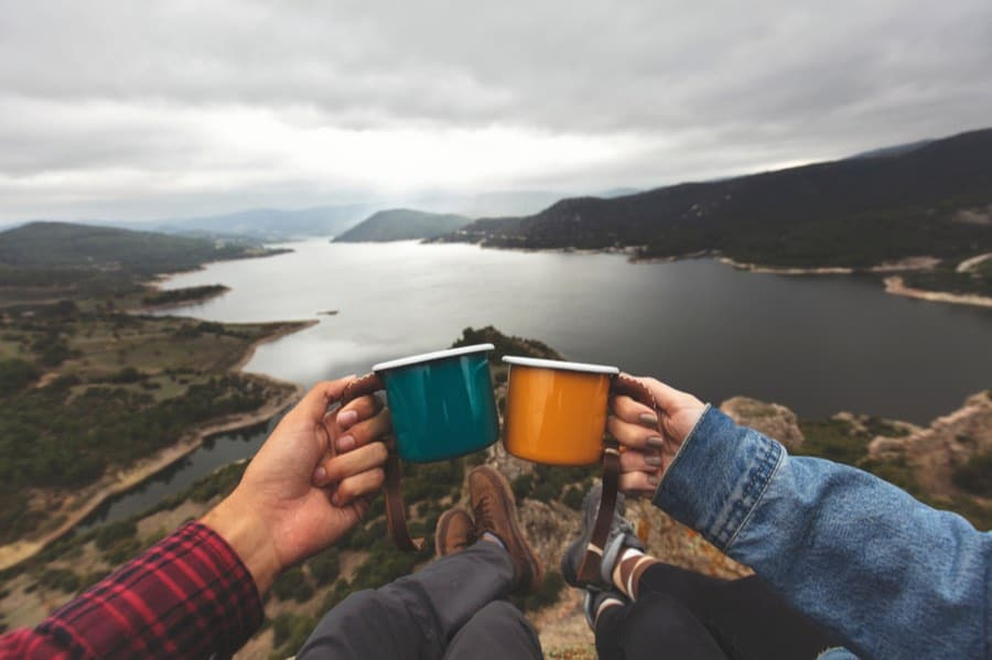 Two People Holding Mugs of Camp Coffee With Beautiful View in Background