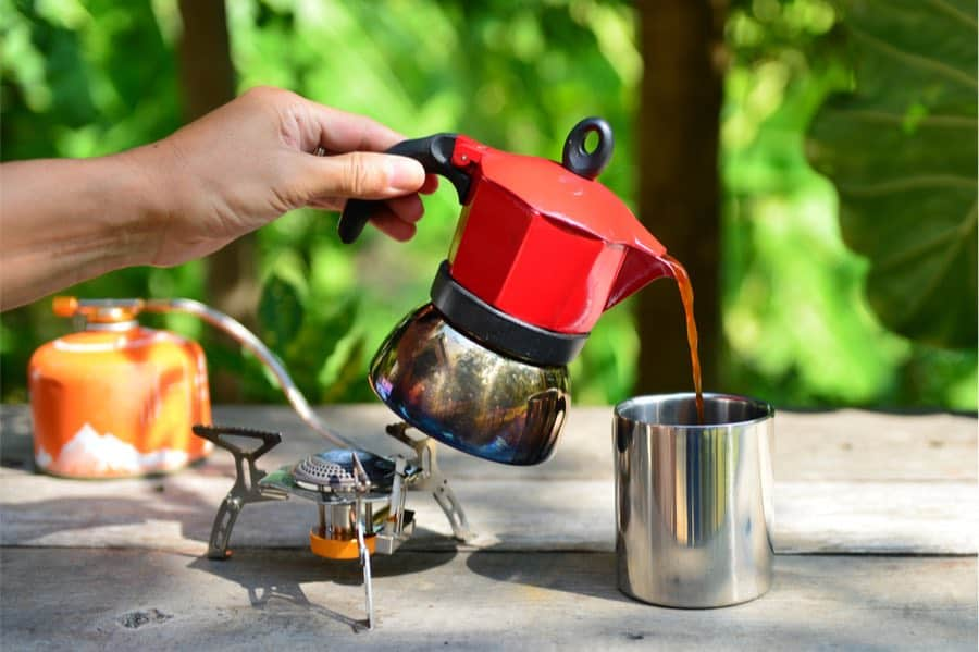 Pouring Water from Camp Coffee Maker into Coffee Cup