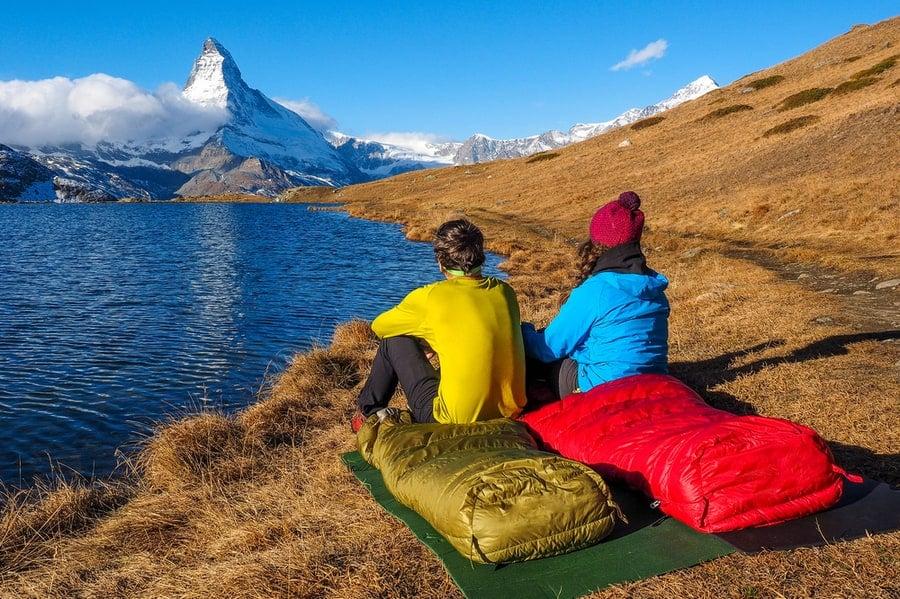 people sitting in sleeping bags looking at a lake