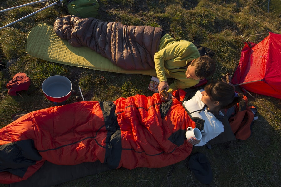 Two People Laying in Sleeping Bags Outdoors