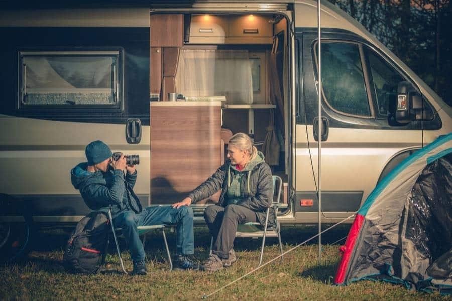 Couple Sitting in Front of RV Camper Van