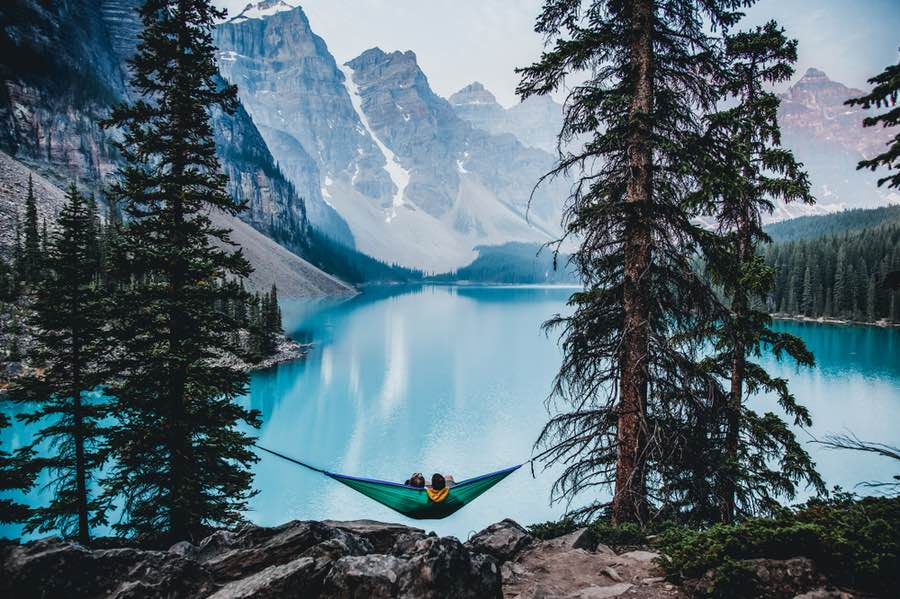 Two People Lounging in Hammock Near Lake Moraine