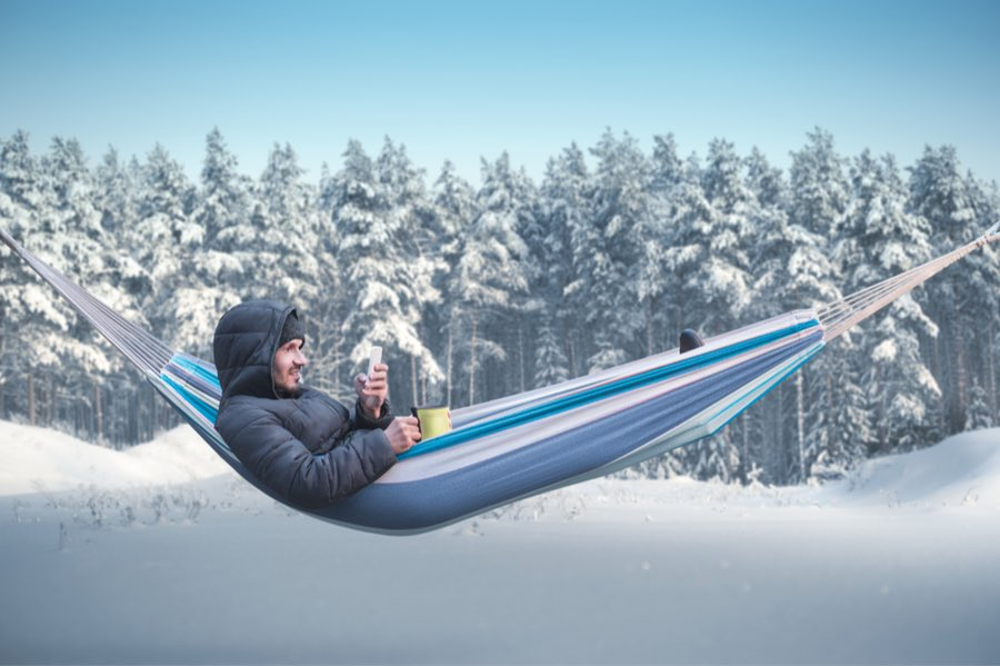 Man Lounging in Hammock in Winter Snow