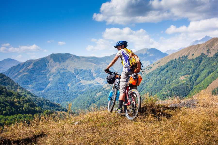 Cyclist Enjoying View While Bikepacking in Mountains