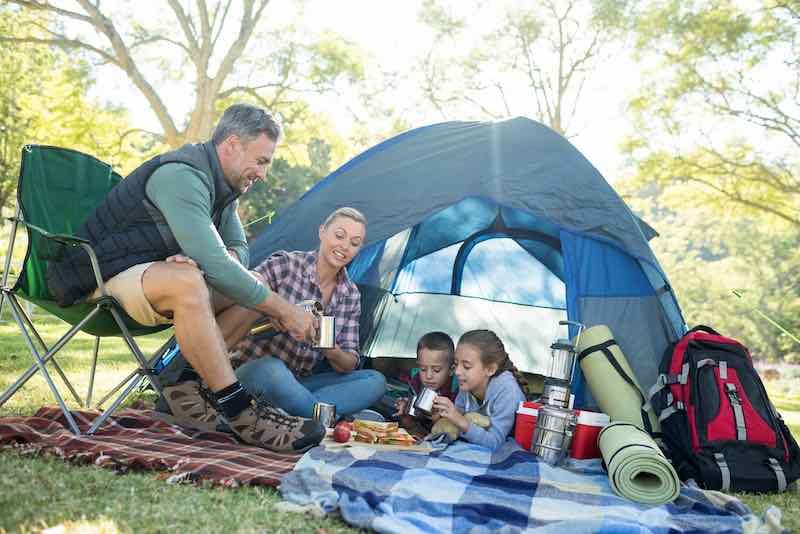 family having snacks outside of tent
