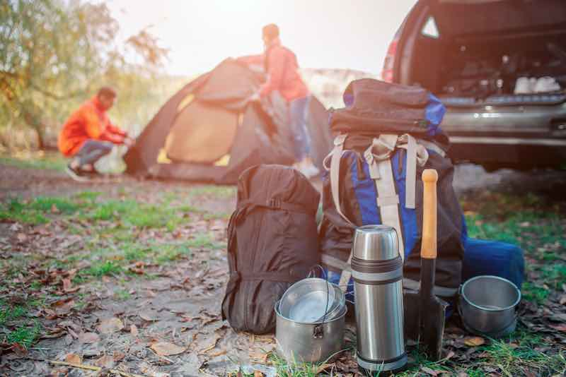 What to pack camping - camping gear by a car.